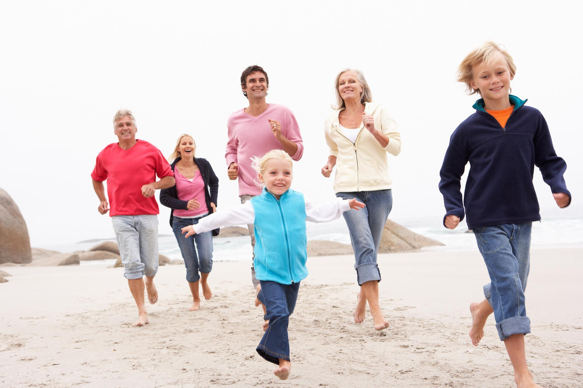 Three generations of a family running along the beach